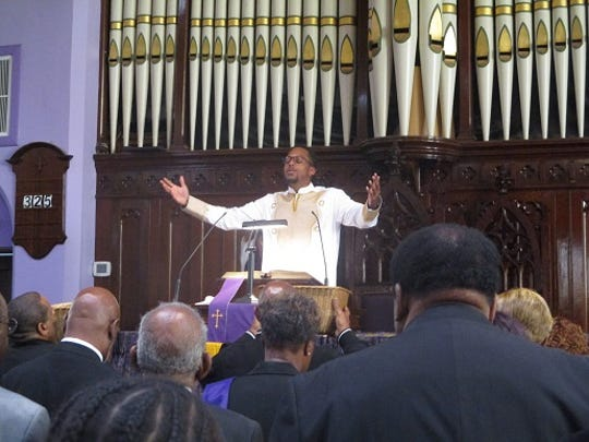 Pastor Weldon McWilliams IV leads Christ Temple Baptist Church in worship after the congregation returned to its Hopper Street home, which had been damaged by a fire.