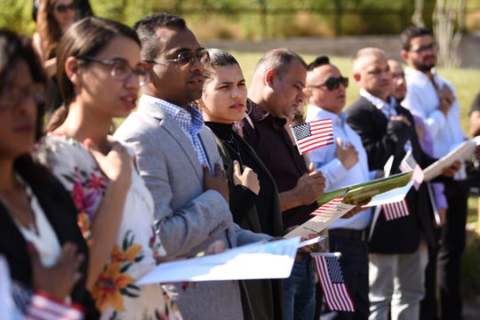 Participants say the Pledge of Allegiance during a Naturalization Ceremony held by the Paterson Great Falls National Historical Park in the new amphitheater of Paterson Great Falls National Historical Park on 10/02/19.