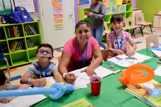A mother and her children enjoy the Kids' Korner at the event at the Fiesta de Salud para Familias community health fair at New Mexico Family Services in Sunland Park in August 2019.