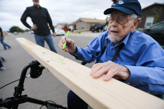 "Malcom ""Mac"" Fell writes blessing on a part of a new home at an event for a Habitat for Humanity groundbreaking at a house site in Las Cruces on Tuesday, Oct. 1, 2019."