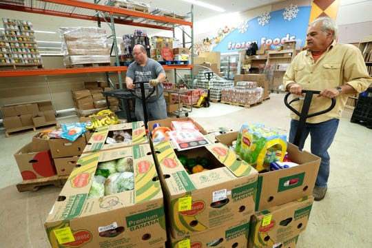 Volunteers Chris Boelter, left, and Neil Verwey deliver a variety of food items donated by local grocery stores through Direct Connect on Oct. 2 at the Oshkosh Area Food Pantry in Oshkosh. Dan Powers/USA TODAY NETWORK-Wisconsin