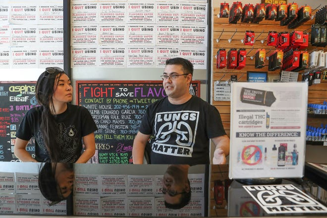 Russ Smelsor and Victoria Drower use several types of displays at Desert Vapors shop in Palm Desert, Calif., on Oct. 1, 2019.
