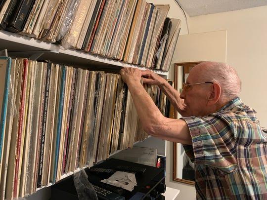 Dr. John Norman looks through his album collection.