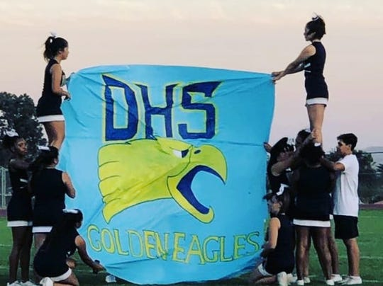 Cheerleaders unveil replica of new logo.