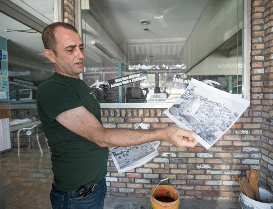 Owner Ray Sehweil  shows photographs that he plans on displaying at the new location of Taste of Jerusalem on W Cervantes Street in Pensacola on Wednesday, October 2, 2019.  Sehweil is in the process of moving from his current location on Pace Blvd. to the former location of Oscar's restaurant/Uncle Billy's Antique Mall.