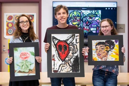 (From left) Hanover High School seniors Abigail Lawrence, Owen Smith and Lydia Hobson pose for a photo with one of their works on September 18, 2019. All three students are enrolled in Marie Smith's AP art class.