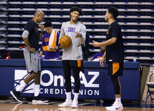 Forward Kelly Oubre, Jr., laughs with guard Devin Booker during Phoenix Suns practice as head coach Monty Williams walks past at the Rolle Activity Center at Northern Arizona University in Flagstaff, Wednesday, October 2, 2019.