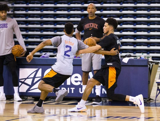 Guard Devin Booker, right, dribbles upcourt as guard Elie Okobo defends during the Phoenix Suns practice at the Rolle Activity Center at Northern Arizona University in Flagstaff, Wednesday, October 2, 2019.