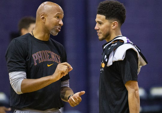 Head coach Monty Williams speaks with guard Devin Booker during Phoenix Suns practice at the Rolle Activity Center at Northern Arizona University in Flagstaff, Wednesday, October 2, 2019.