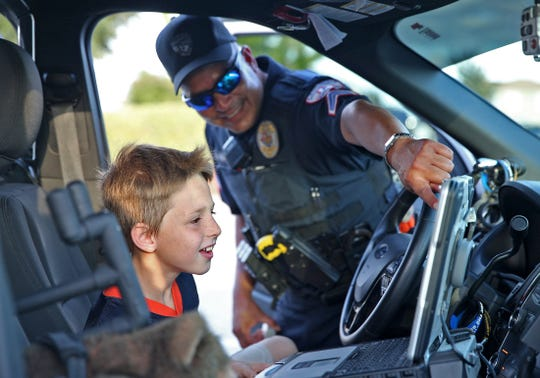 San Angelo police officer Albert Alvarez, center, shows Colton Moore, left, how to work the sirens in his patrol vehicle during the National Night Out event at Goodfellow Family Housing on Tuesday, Oct. 1, 2019.