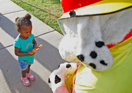 Samari Shields, left, isn't quite sure what to make of the San Angelo Fire Department mascot during the National Night event at Goodfellow Family Housing on Tuesday, Oct. 1, 2019.