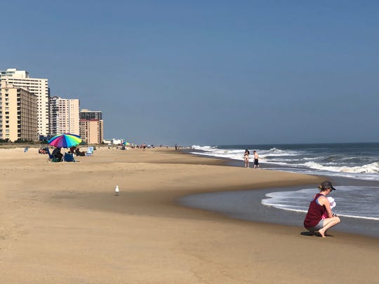 A few beach-goers brave a blazing sun on a day that is unusually hot for Oct. 2.