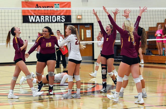 Roosevelt High School volleyball players celebrate winning a game during a match against Washington on Tuesday, October 1, in Sioux Falls.