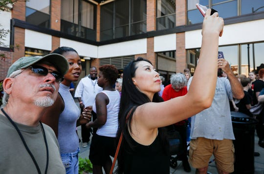 Saehee Duran, center, takes a photo of the historical marker on Park Central Square on Wednesday, Oct. 2, 2019, that honors three African American men, Horace Duncan, Fred Coker, and William Allen, who were lynched in downtown Springfield in 1906.