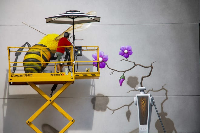 """Arkansas artist Jason Jones paints """"The Pollinator"""" in an undated photo from 2019. The 25-foot mural is located at Farmers Park in southeast Springfield, Mo."""