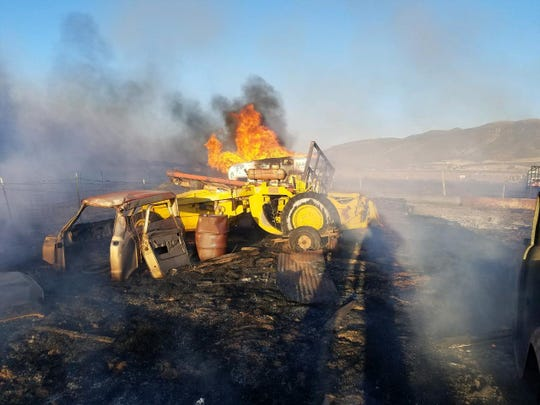 A fire burned several vehicles and farm implements and threatened more than a dozen homes Tuesday in Iron County after someone using an acetylene torch set dry grass in the area on fire.