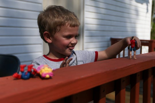 Johnnie Clark's great grandson Trenton Hostetter, 3, plays with his toys on the deck outside Clark's home, which was heavily damaged by Hurricane Michael, one year later on Wednesday, Oct. 2, 2019.