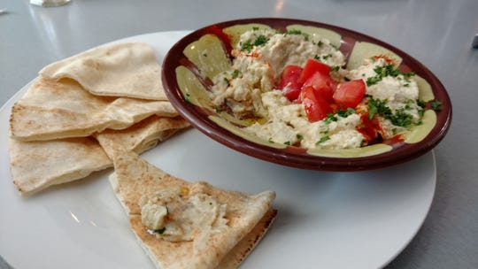 Hummus flatbread at Sammy's Mediterranean Café is a large pita spread generously with hummus and baked before being topped with shredded lettuce and tomatoes.