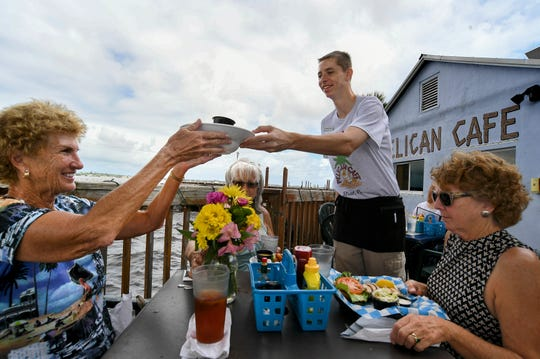 "Brandon Jasuta (center), server at the Pelican Cafe, delivers lunch to Sally Gabriel (from left), Linda Russell, and Polly Patterson, all of Stuart, during a birthday lunch for Gabriel on Wednesday, Oct. 2, 2019, at the restaurant in downtown Stuart. The Pelican Cafe is facing a challenge on extending their short 5-year lease with the city, which expires in 2021. ""I would say they've been here all these years, they've done a good job, it's a popular spot, it's nice, charming, laid back, quaint, old Florida, and I think that's important for Stuart, to retain that,"" Gabriel said. ""It's a small business, I think we should reward people who have done a good job."""