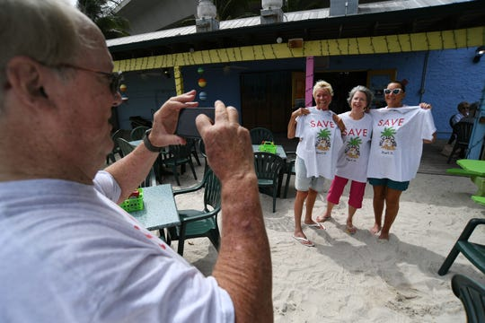 Pelican Cafe co-owner Paul Daly, (from left) takes a photo with his wife and co-owner Linda Daly, with their friends and customers Sharyn and Becky Cerniglia, holding their buisness t-shirts after lunch on Wednesday, Oct. 2, 2019, in downtown Stuart. Located near the southeast corner of the Roosevelt Bridge, the Pelican Cafe overlooks the St. Lucie River, giving its customers a relaxing view of the waterway, just north of Flagler Park in downtown Stuart. The cafe is facing a challenge on extending their short 5-year lease with the city, which expires in October 2021.