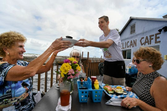 Brandon Jasuta (center), server at the Pelican Cafe, delivers lunch to (from left) Sally Gabriel, Linda Russell and Polly Patterson, all of Stuart, during a birthday lunch for Gabriel on Wednesday, Oct. 2, 2019, at the restaurant in downtown Stuart.