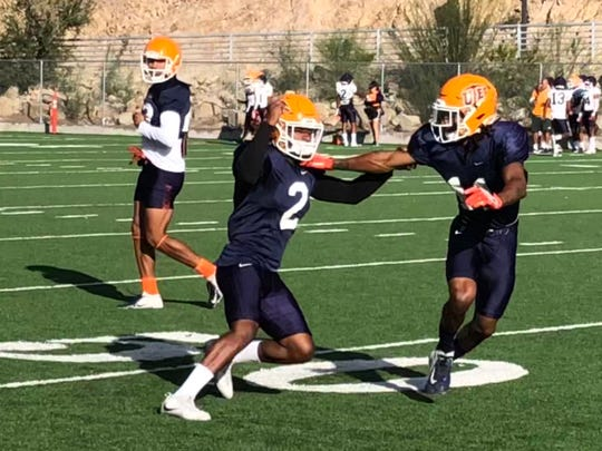 UTEP junior receiver Devaughn Cooper (2) battles against Tre'Shon Wolf in a Wednesday drill at Glory Field