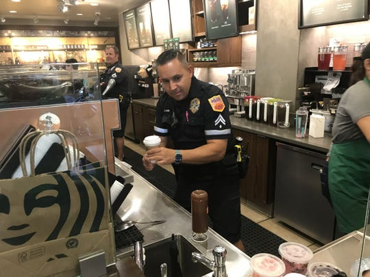 Officer Charles Burns tried his hand at making lattes on Wednesday with help from the Starbucks crew.