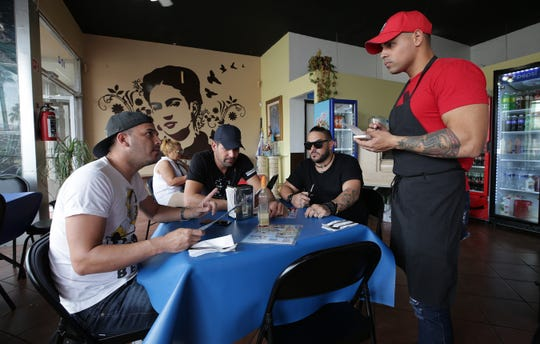 Cuban asylum seeker Fernando Calana works as a waiter at the Caribbean Queen, a Cuban restaurant in downtonwn Juarez. Other Cubans awaiting hearings in the US frequent the restaurant looking for the taste of home.