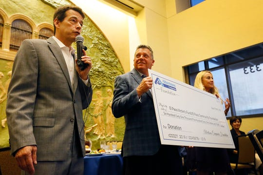 Eric Pearson, left, CEO of the El Paso Community Foundation, accepts a $661,561 check for the El Paso shooting victims' fund from Albertsons executives Keith Jones and Nancy Keane during an Oct. 2, 2019, luncheon to honor first responders to the Aug. 3 Walmart mass shooting.