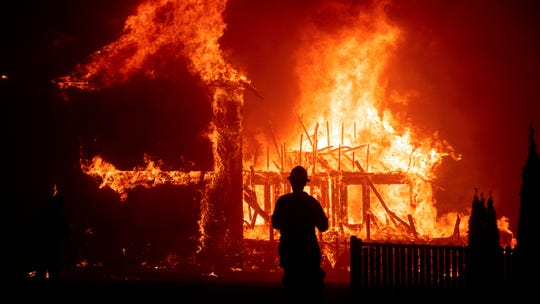 In this Nov. 8, 2018, file photo, a home burns during a wildfire in Paradise. Gov. Gavin Newsom has signed, Wednesday, Oct. 2, 2019, nearly two-dozen laws aimed at preventing and fighting the devastating wildfires that destroyed the Sierra foothills city last fall.