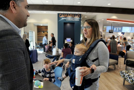 Dunkin' Donuts customer Jennie Spears, right, talks with Aharon Aminpour, CEO of Madison Foods, during the opening of his Dunkin' Donuts inside the CBC Federal Credit Union branch in Camarillo. Spears is holding son Luke Spears, 8 months old, while  Jack Spears, 3 1/2, looks on.