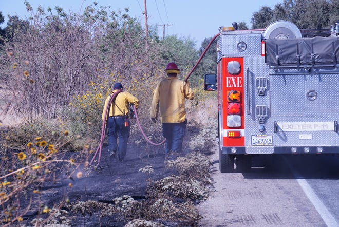 Tulare County Fire Department crews work to put out a roadside fire near Exeter that delayed traffic in the area.
