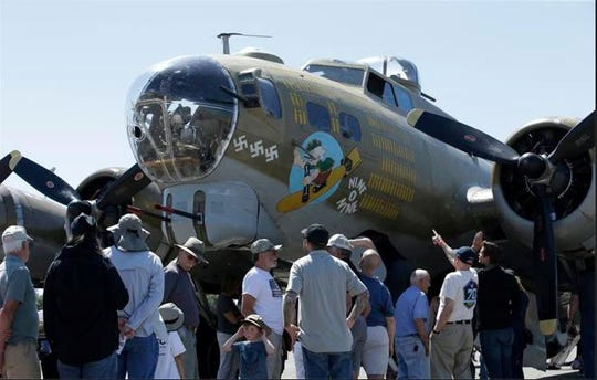 "In this June 2, 2018, photo, people look over the Nine-O-Nine, a Collings Foundation B-17 Flying Fortress, at McClellan Airport in Sacramento, California. A B-17 vintage World War II-era bomber plane crashed Wednesday, Oct. 2, 2019, at Bradley International Airport  in Windsor Locks, Connecticut. Airport officials said the plane was associated with the Collings Foundation, an educational group that brought its ""Wings of Freedom"" vintage aircraft display to Bradley. ("