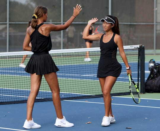 Rider's Julia Chon, right, high-fives Axelle Jacquemin during their doubles match against Wichita Falls High Tuesday, Oct. 1, 2019, at Old High.