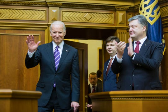 Ukrainian President Petro Poroshenko, right, applauds to U.S. Vice President Joe Biden, left, after he addressed the Ukraine Parliament in Kiev, Ukraine, Tuesday, Dec. 8, 2015.