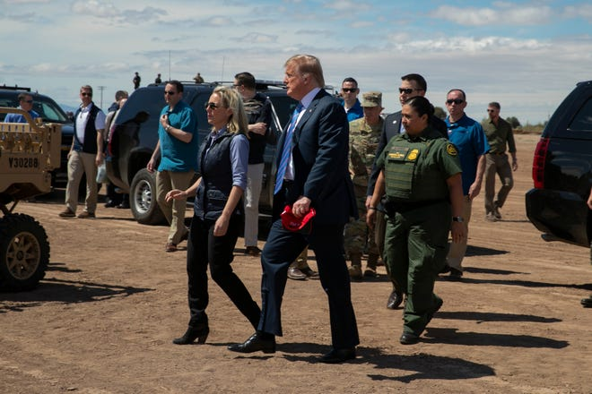 President Donald Trump walks with Homeland Security Secretary Kirstjen Nielsen during an April visit to the border.