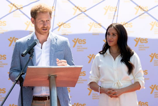 Prince Harry delivers a speech at the Youth Employment Services in Johannesburg, South Africa, on Oct. 2, as Duchess Meghan watches.