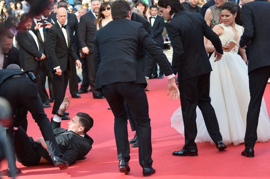 """Vitalii Sediuk is dragged away after he tried to slip under actress America Ferrera's dress during the screening of """"How to Train your Dragon 2"""" on May 16, 2014."""