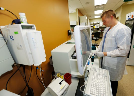 In this Thursday, March 9, 2017, photograph, lab technician Zach Meili works in Denver Health Medical Center's primary care clinic located in a low-income neighborhood in southwest Denver.