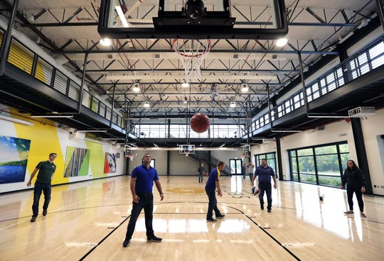 Employees play basketball in the gymnasium of the new Secura headquarters building in Fox Crossing.