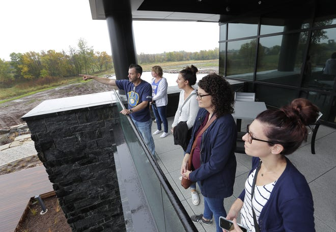 Facilities manager Clint Dusenbery points out sweeping views to fellow employees from a balcony at the new headquarters in Fox Crossing.