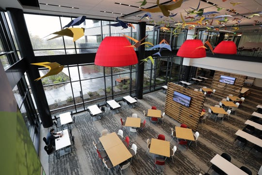 Colorful bird sculptures and oversized lighting fixtures brighten the company cafe in the new headquarters of Secura in Fox Crossing.