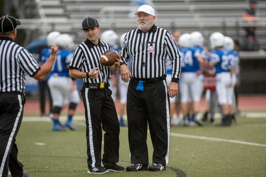 Jim Hughes and his son Aaron Hughes work an 8th grade football game together at Harper Creek High School on Wednesday, Oct. 2, 2019 in Battle Creek, Mich. Aaron is a baseball player who is spending the fall season working as a football referee.