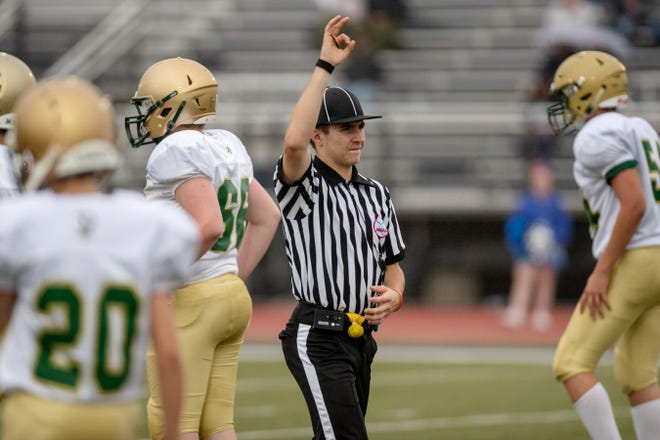 Lakeview junior Aaron Hughes calls a third down during an 8th grade football game between Harper Creek and Jackson Lumen Christi on Wednesday, Oct. 2, 2019 at Harper Creek High School in Battle Creek, Mich. Aaron is a baseball player who is spending the fall season working as a football referee alongside his father.