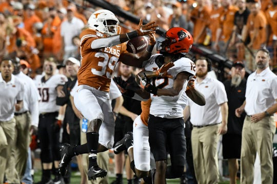 Texas Longhorns defensive back Montrell Estell (39) breaks up a pass intended for the Oklahoma State Cowboys Kanion Williams (12) in the second half at Darrell K Royal-Texas Memorial Stadium.