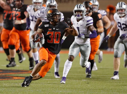 Oklahoma State Cowboys running back Chuba Hubbard (30) runs for a first down ahead of Kansas State Wildcats linebacker Eric Gallon II (1) during the second half at Boone Pickens Stadium. Oklahoma State won 26-13.