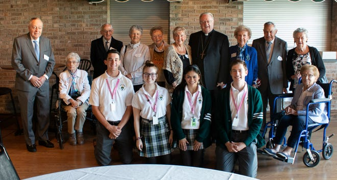 Bishop Dennis Sullivan attends an alumni Mass with Camden Catholic High School students and 70-year-plus graduates, including Dorothea Marie Reigert (to bishop's right), class of 1936; and Reigert's sister, Mary Moore Olsen (to bishop's left), class of 1942.