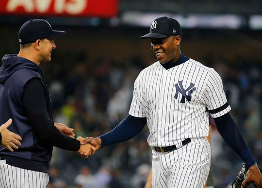 New York Yankees relief pitcher Aroldis Chapman (54) is congratulated by manager Aaron Boone after getting the save against the Boston Red Sox at Yankee Stadium on June 1, 2019.