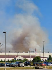 A brush fire along the railroad tracks creates a pillar of smoke behind the industrial park on Thursday, Oct. 3, 2019.