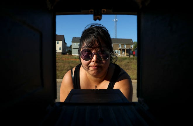 Jimyoung Kim, a new resident who's mailbox was taken after she and her husband signed on the home, peers into a mailbox in her neighborhood for a portrait on Christian James Court in Clarksville, Tenn., on Wednesday, Oct. 2, 2019.